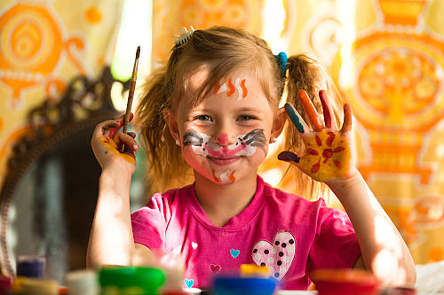 young girl having fun with painting pictures on her face and hands